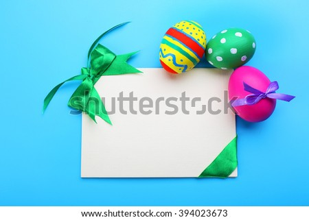 Easter eggs with greeting card on blue background - stock photo