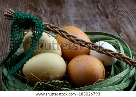Easter fresh eggs in green basket - nest with czech whip on woooden desk / background - stock photo