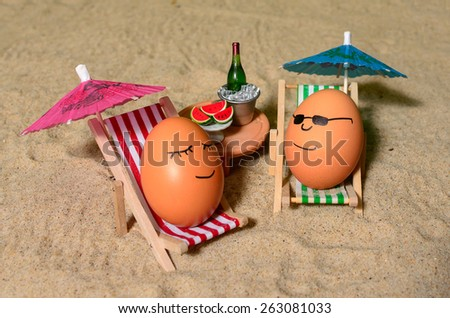easter funny eggs sitting on a chair under umbrella on a sand and bottle of champagne in a  bucket. selective soft focus - stock photo
