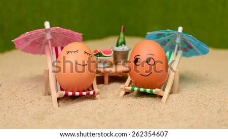 easter funny eggs sitting on a chair under umbrella on a sand and bottle of champain in a  bucket with watermelon. selective soft focus - stock photo