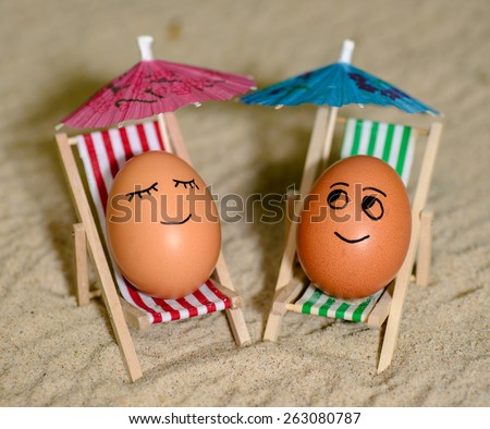 easter funny eggs sitting on a chair under umbrella on a sand. selective soft focus - stock photo