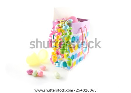 Easter gift bag with candy, gift card, and easter eggs over a white background. - stock photo