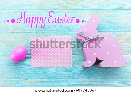 Easter greeting card. Pink egg and rabbit on blue wooden background - stock photo