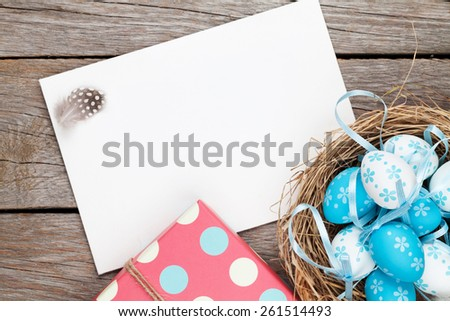 Easter greeting card with blue and white eggs and gift box over wood. Top view with copy space - stock photo
