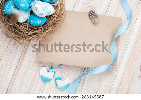 Easter greeting card with blue and white eggs in nest and decor. Top view with copy space - stock photo