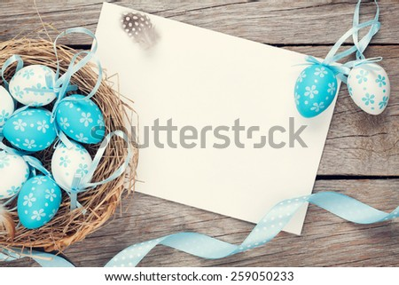 Easter greeting card with blue and white eggs in nest over wood. Top view with copy space - stock photo