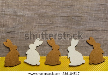 Easter greeting card with rabbits on the wooden frame. - stock photo