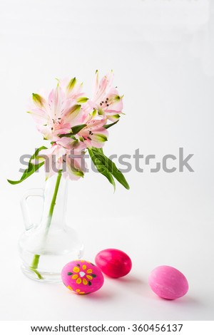 Easter hand-painted pink eggs with light delicate pink flowers in a glass vase on white background. Easter background. Easter symbol. Top view with copy space. Vertical - stock photo