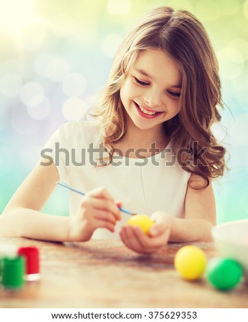 easter, holiday and child concept - happy girl with brush coloring easter eggs over lights background - stock photo