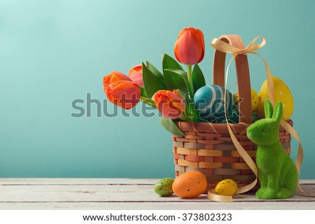 Easter holiday basket with eggs, flowers and easter bunny - stock photo