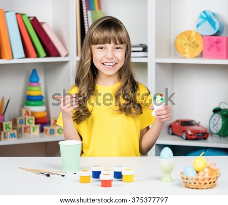 Easter holiday - beautiful smiling little girl with brush coloring eggs for easter - stock photo