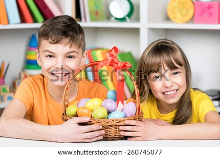 Easter holiday - cute children with basket of Easter eggs - stock photo