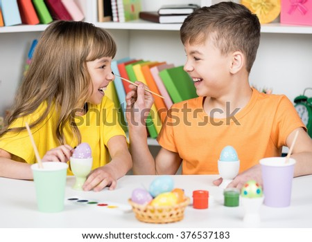 Easter holiday - cute happy children coloring eggs for easter at home - stock photo