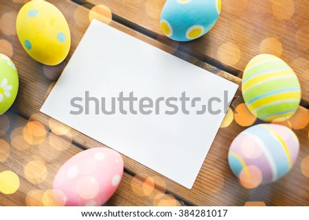 easter, holidays, tradition and object concept - close up of colored easter eggs and blank white paper card on wooden surface with copy space over lights - stock photo