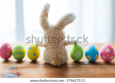 easter, holidays, tradition and object concept - close up of colored easter eggs and bunny - stock photo