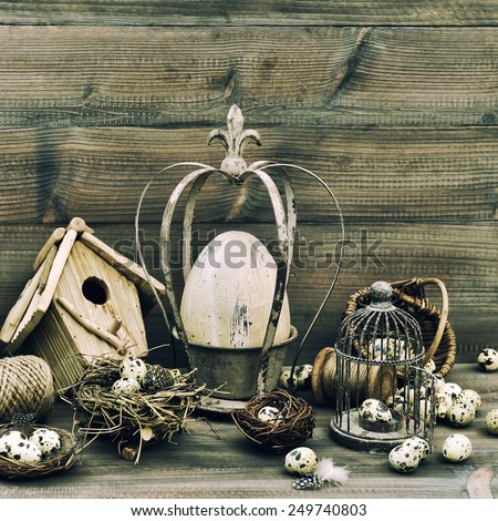 Easter home decoration with eggs, nest and birdcage. Vintage style toned picture - stock photo
