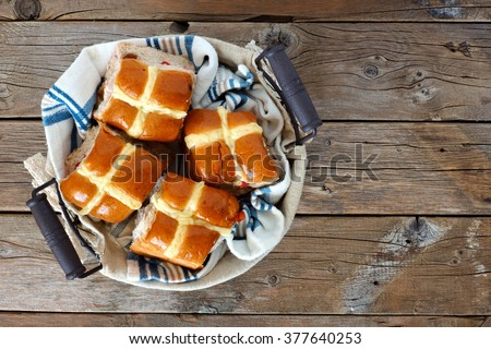 Easter Hot Cross Buns in a basket, downward view on a rustic wood background - stock photo