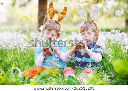 Easter kids eating chocolate bunnies. - stock photo