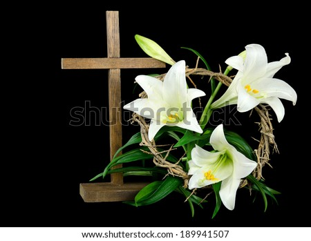 Easter lily with wooden cross and crown of thorns on a black background - stock photo