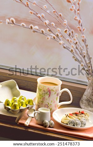 Easter morning with pussy-willow in the vase, candy eggs and coffee, toned - stock photo