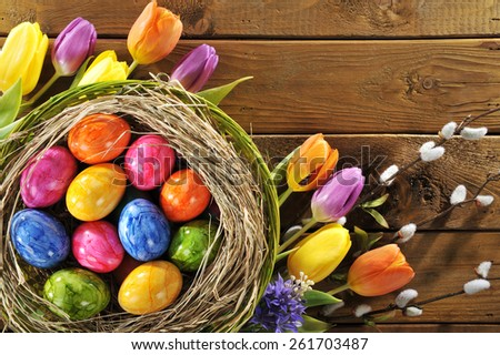 Easter nest with many colored henâ??s eggs, tulip, hyacinth and pussy willow on old wooden board - stock photo