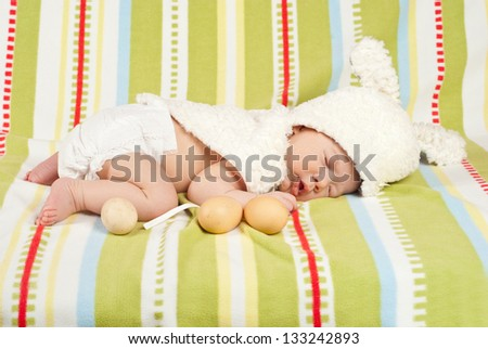 Easter newborn baby boy sleeping on blanket with fresh eggs near him - stock photo