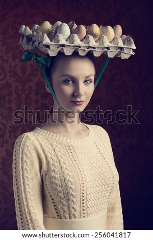 easter portrait of pretty brunette girl with yellow dress and bizarre hat with coloured eggs in carton box - stock photo