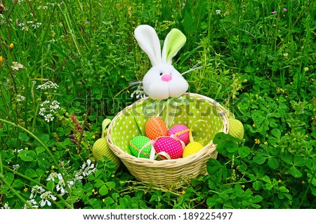 easter rabbit and eggs on the green grass - stock photo