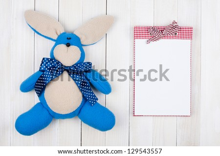 Easter rabbit and notepad on white wood background - stock photo