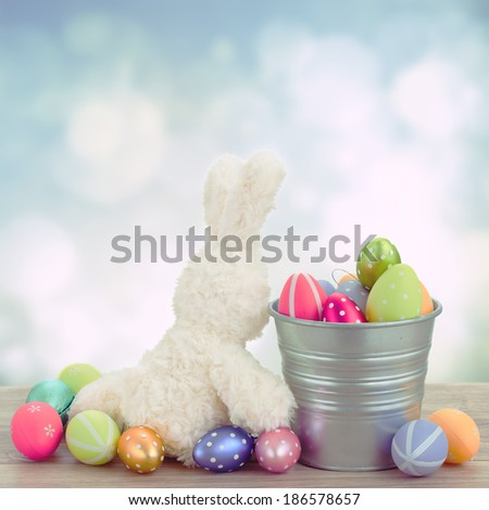easter rabbit  with metal pot full of  eggs on blue background - stock photo
