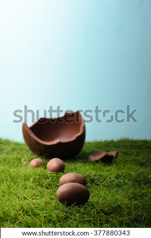 Easter scene with small milk chocolate eggs forming a path up a grassy hill , leading to a larger egg that is broken open.  Blue sky behind and above provides  copy space.  The grass is artificial. - stock photo