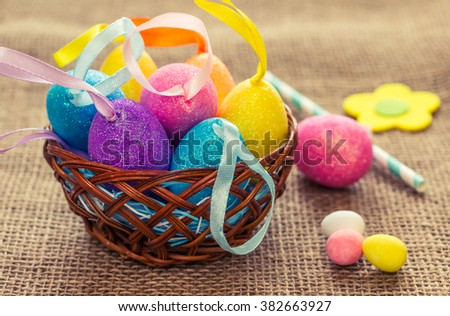 Easter still life with decorative eggs. Easter eggs in a wicker basket. Special vintage toning. - stock photo