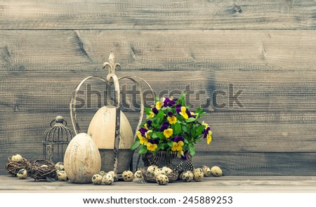 Easter still life with eggs, pansy flowers, nest and birdcage. Vintage style toned picture - stock photo