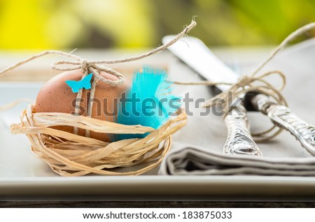 Easter table setting.Egg in nest, natural light, garden background. - stock photo