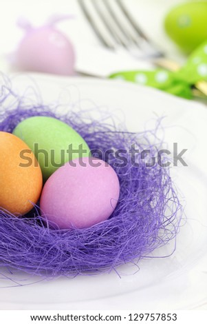 Easter table setting for a festive dinner - a decorative purple nest with colourful Ester eggs on a plate - stock photo