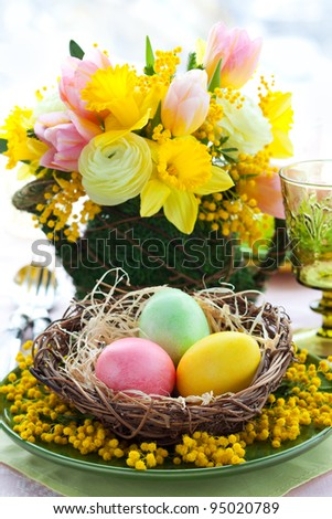 Easter table setting with colored eggs and spring flowers - stock photo