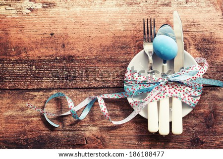 Easter table setting with white plate and easter egg  on old wooden table/ Easter background - stock photo