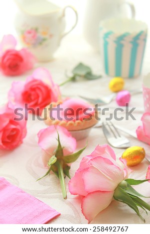 Easter table with sweet eggs, pink roses and fresh cakes - stock photo
