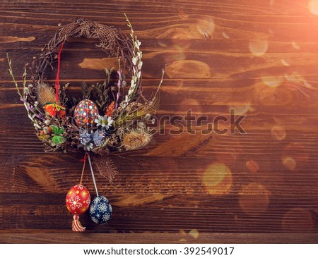 Easter wreath with easter eggs, decorative butterflies, flowers and blooming willow on the wooden background. easter decorations. Happy Easter. soft light effect - stock photo