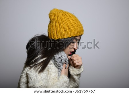 Eastern brunette girl got sick and coughing, hipster in winter clothing, photo studio, portrait of a woman isolated on gray background - stock photo