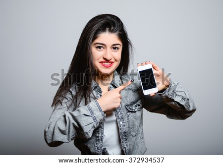 Eastern brunette girl points a finger at mobile phone, hipster denim clothing, photo studio, portrait emotions - stock photo