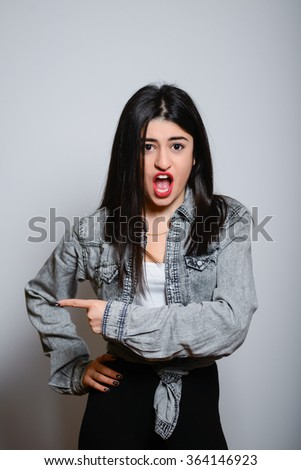 Eastern brunette girl points a finger to the side, hipster denim clothes, isolated studio portrait emotions - stock photo