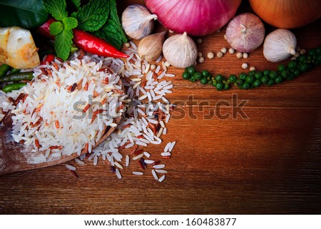 eastern food spice herb rice garlic chilly pepper mint leaves red onion green pepper on wood table background - stock photo