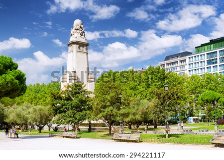 Eastern side of the Cervantes monument on the Square of Spain (Plaza de Espana) in Madrid on the blue sky background with white clouds in summer time. Madrid is popular tourist destination of Europe. - stock photo