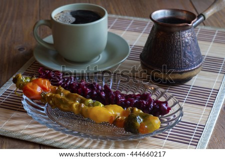 Eastern sweets. Churchkhela. Cup of coffee, coffee pot. - stock photo