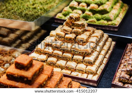 Eastern sweets in a wide range, baklava, Turkish delight with almond, cashew and pistachio nuts on plates - stock photo