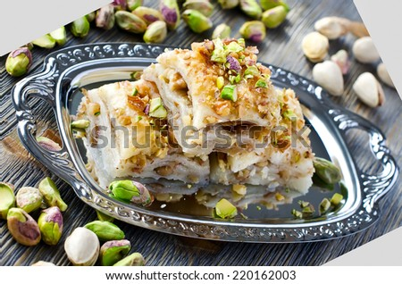 eastern traditional dessert with nuts and pistachios wooden background - stock photo