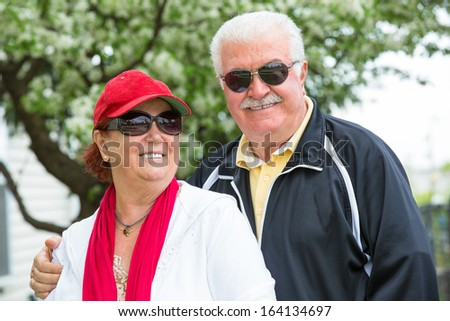 Easygoing positive senior couple posing with their sports clothing and sunglasses in front of blooming spring tree. Man holding his partners shoulder, seems like she enjoys it - stock photo