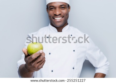 Eat a healthy meal! Happy young African chef in white uniform stretching out green apple and looking at camera with smile while standing against grey background - stock photo