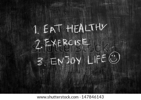Eat healthy and exercise written on blackboard - stock photo